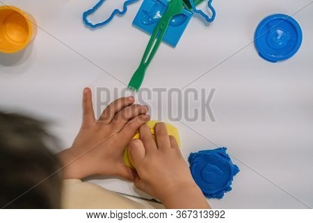 Top View Of Boy Sculpting Plasticine Figures Near Stick And Molds On Table