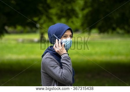 Muslim Woman With Hijab Wearing Face Mask And Talking On Mobile Phone In Nature While Walking Alone