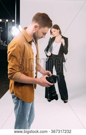 Selective Focus Of Photographer Looking At Display Of Digital Camera Near Elegant Model And Floodlig