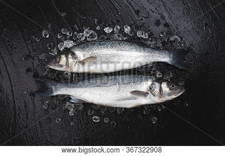 Seabass On Ice On Black Stone Background, Top View