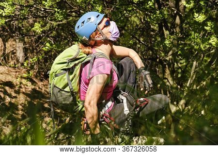 Woman Mountaineer With Helmet, Backpack, And Medical Mask, Enjoys The Fresh Nature Air In A Forest.
