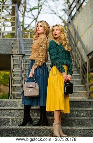Sweater Skirt Trend. Completing Each Other. Matching Outfits. Women Sisters Outdoors Stairs Backgrou