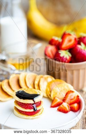 Skewers Of Mini Pancakes With Strawberries And Chocolate. Chocolate Extends To Mini Pancakes. Sweet