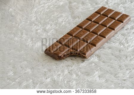 A Bitten Chocolate Bar On A Fleecy White Background. Brown Chocolate Bar Without A Wrapper. Pleasure
