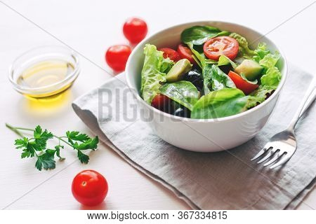 Fresh Salad Of Avocado, Cherry, Arugula And Olives Made At Home. Vegan Food. The Concept Of Healthy