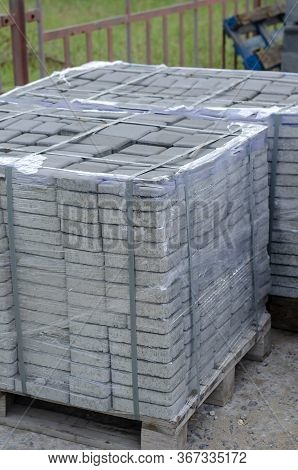 Pallet Of New Paving Slabs Outdoors. The Pallets With The Packed Gray Paving Slabs Are Pulled Togeth