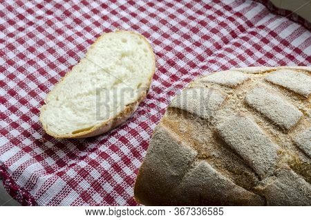 Freshly Baked Homemade Bread On A Red And White Towel. A Loaf Of Sliced Bread And A Loaf Sprinkled W