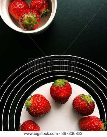 Strawberries on a black plate and a white ramekin