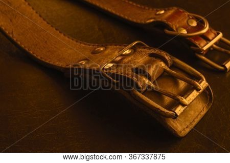 Fragment Of Two Old Genuine Leather Collars On A Dark Table. Cracked Shabby Leather And Metal Fittin