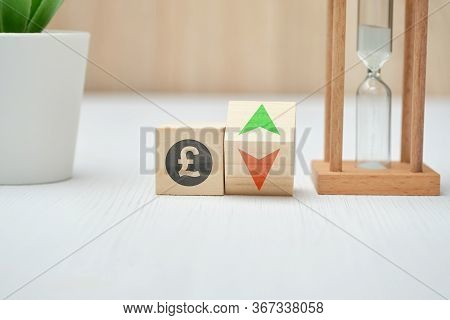 Wooden Blocks With Gbp Pound Sterling Sign And Up And Down Arrows. Close Up.