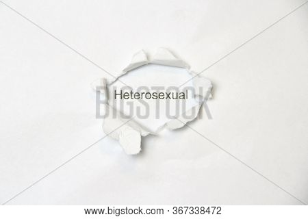 Word Heterosexual On White Isolated Background, The Inscription Through Wound Hole In Paper. Concept