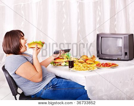 Overweight woman eating fast food and watching TV.