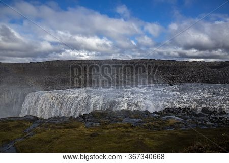 General View Of Dettifoss, The Most Powerful Waterfall In Europe. The Sky Is Royal Blue With Clouds.