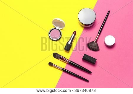 Professional Makeup Brushes, Powder, Eyeshadow, Blush, Lipstick On Yellow Pink Background Flat Lay T