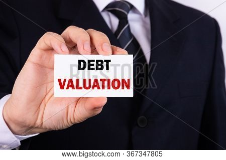 A Businessman Is Holding A Tablet With The Text Debt Valuation In Front Of Him In His Hands. Busines