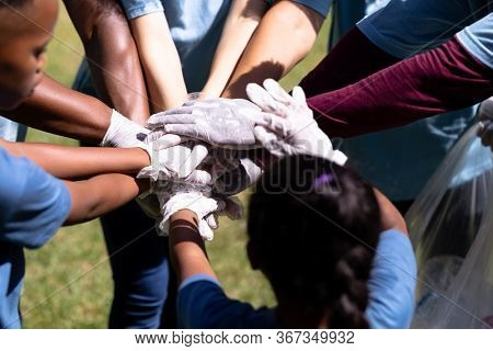 Multi-generation mixed race family spending time outside together, all wearing blue volunteer t shirts and protective gloves, collecting garbage, standing in a huddle, hand stacking, on a sunny day