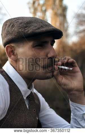 Retro 1920S Portrait Of An English Gangster With A Flat Cap. Smokes A Cigarette On The Street.