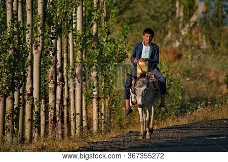 Istaravshan. Tajikistan. August 06,2019. A Young Man Riding A Donkey Rides Along The Pamir Highway.