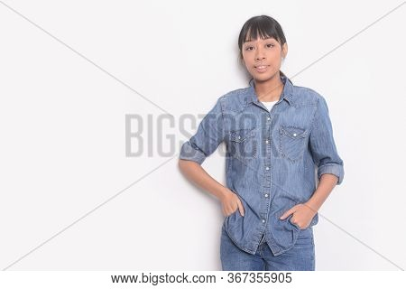 young woman in jeans shirt with blue jeans  isolated with hands holds pockets standing on white background,