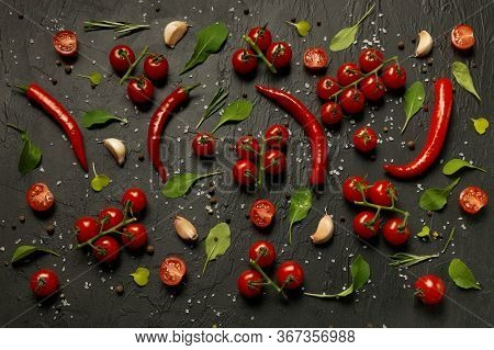 A Lot Of Cherry Tomatoes, Hot Pepper Pods, Leaves Of Rucola And Salad, Garlic And Lie On A Black Bac