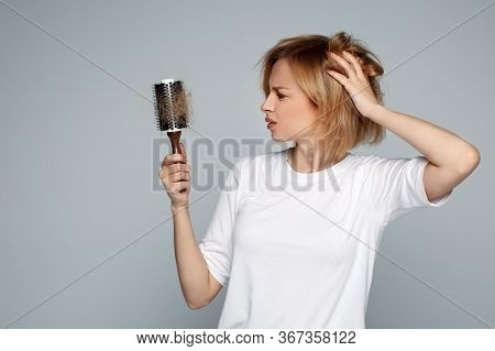 Blonde Young Worried Woman Holding Hairbrush With Unexpected Hair Loss Problem, Alopecia, Worried An