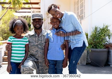 African American male solider wearing uniform and his family standing by their house on a sunny day, smiling and looking straight into a camera.