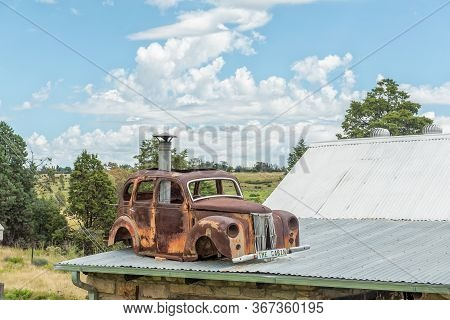 Clocolan, South Africa - March 20, 2020: A Vintage Rusted Car Is Visible On The Roof Of The Cabin Ro