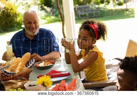 Side view of a young African American girl holding a glass sitting at a table with her young brother and smiling grandfather for a family meal outside on a patio in the sun
