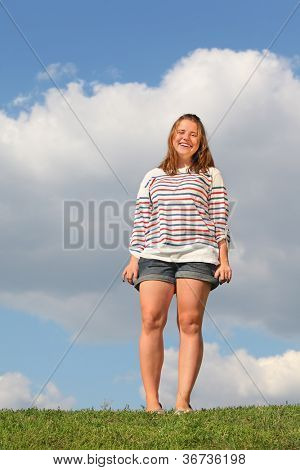 Young fat girl in shorts stands at green grass and laughs at background of blue sky.