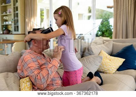 Side view of a senior Caucasian man at home in the living room on the couch, his granddaughter kneeling beside him and helping him to put on VR googles