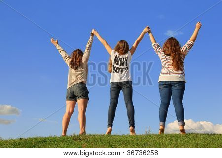 Back of three girls holding hands at green grass at background of blue sky.
