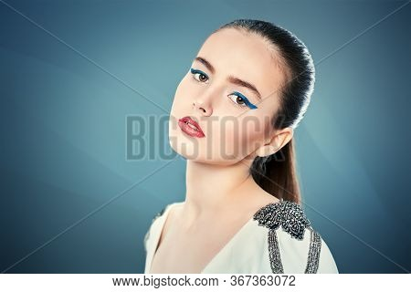 Fashion shot. Portrait of a beautiful young woman in white jacket on a grey background. Trendy makeup with blue aquamarine eye arrows. Make-up and cosmetics.