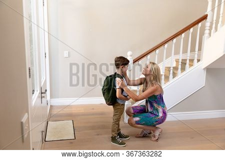 Side view of a Caucasian woman kneeling in the hallway smiling and preparing her young son to leave for school, the son is wearing a backpack