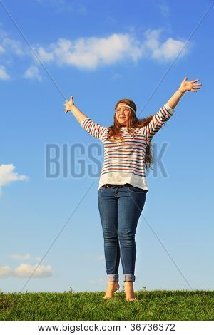 Young girl in jeans raises her hands at green grass at background of blue sky.