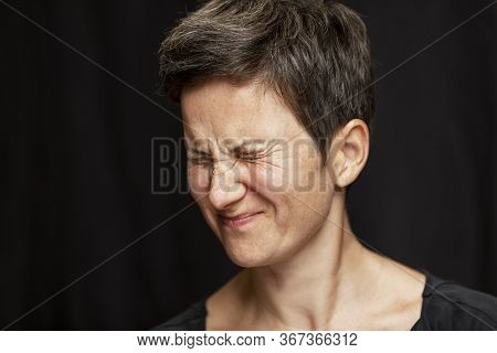 A Woman With A Short Haircut And Gray Hair Is Emotionally Angry By Squinting Her Eyes. Anger And Rag