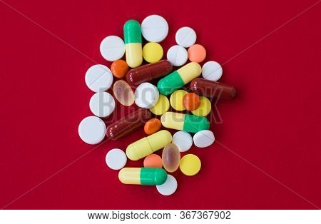 Medical Background With Pills And Capsule On Red Background.assorted Pharmaceutical Medicine Pills,