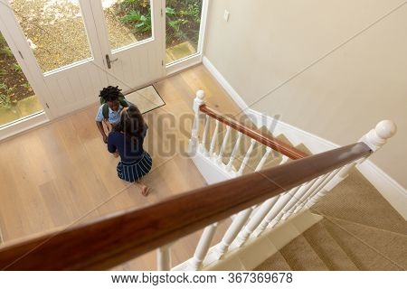 High angle view of a mixed race woman at home, kneeling in the hallway by the front door, preparing and saying goodbye to her young son, before he leaves for school with his backpack on