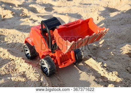 Toy Loader On The Beach. Orange Toy Excavator Raking Sand. The Concept Of Summer Holidays, Vacations