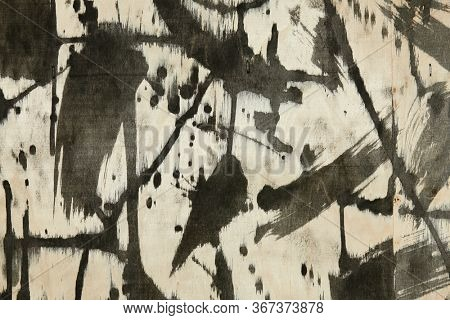 abstract grunge background, artistic painting with black paint on a light wooden background, abstract strokes and spots in a chaotic style