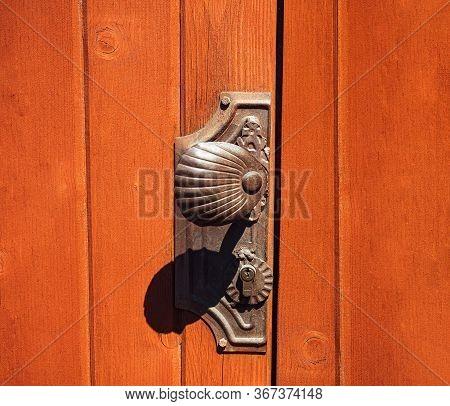 Antique Doorknob On A Wooden Door, Closeup. Antique Metal Door Handle. Old Wooden Entrance Door With