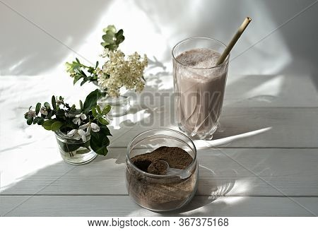 Whey Drink In A High Glass. Whey Protein Chocolate Cocktail. A Jar With Protein Powder And Flowers O