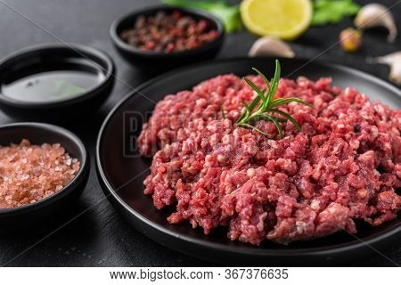 Fresh Minced Meat Ground Beef On A Black Plate Against Stone Background.