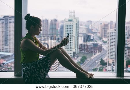 Woman using mobile phone relaxing by condo window at home or office room silhouette. Business woman at work pensive looking at cellphone social media app. Mental health online addiction concept.