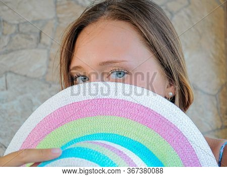Close-up Portrait Of A Brunette Covering Half Of Her Face With A Straw Hat And Looking At The Camera