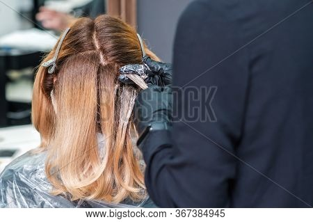Hair Coloring Of Young Woman By Hands Of Hairstylist Close Up.