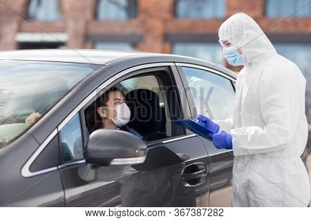 medicine, quarantine and pandemic concept - doctor or healthcare worker in protective gear or hazmat suit, medical mask, gloves and goggles with clipboard and woman in car waiting for coronavirus test