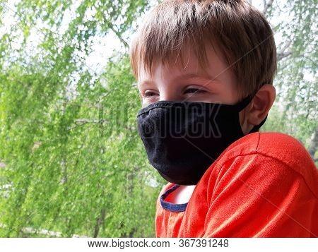 Kids In Face Mask Sad Near Window. Boy In Red T-shirt Wear Protective Mask During Coronavirus. Child