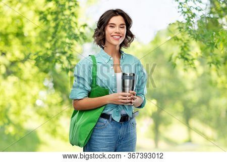 sustainability, eco living and people concept - portrait of smiling young woman with green reusable canvas bag for food shopping and tumbler or thermo cup over green natural background