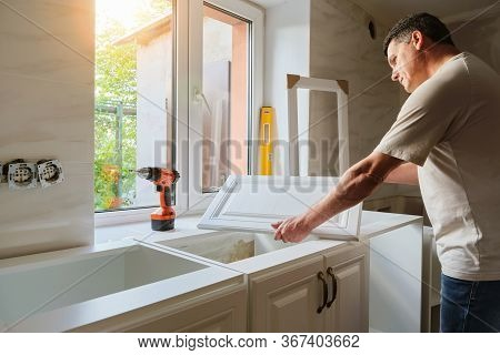 Middle-aged Caucasian Man Holds The Door Of The Kitchen Cabinet, Preparing For The Process Of Custom