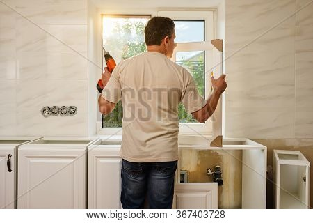 Middle-aged Caucasian Man Stands With His Back And Holds The Kitchen Cabinet Door And Cordless Screw